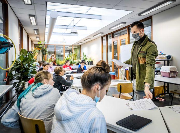 Een leraar van een middelbare school draagt een mondkapje in de klas.