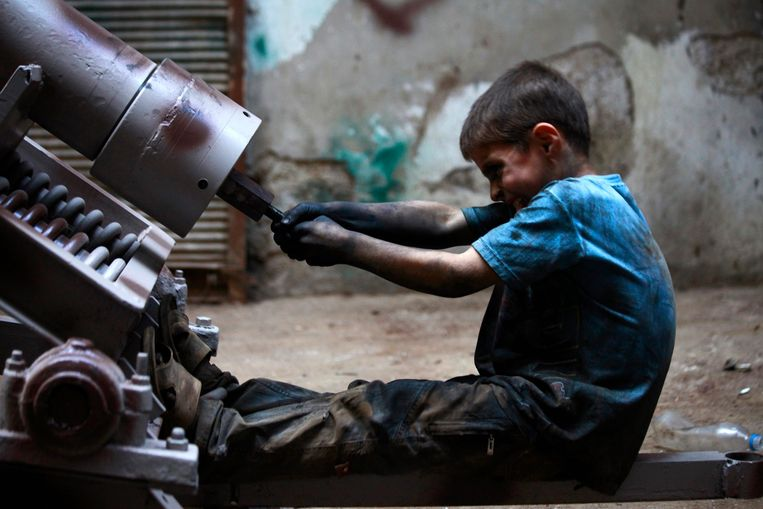 Issa, 10 years old, fixes a mortar launcher in a weapons factory of the Free Syrian Army in Aleppo, September 7, 2013.  Issa works with his father in the factory for ten hours every day except on Fridays. REUTERS/Hamid Khatib (SYRIA - Tags: POLITICS CONFLICT CIVIL UNREST) Beeld REUTERS