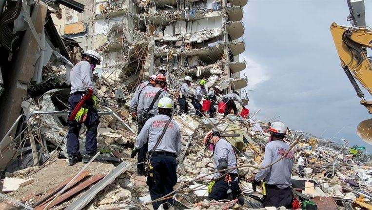 Reddingsploegen werken op de instabiele bergen cement en staal in de hoop overlevenden te vinden.  Beeld via REUTERS