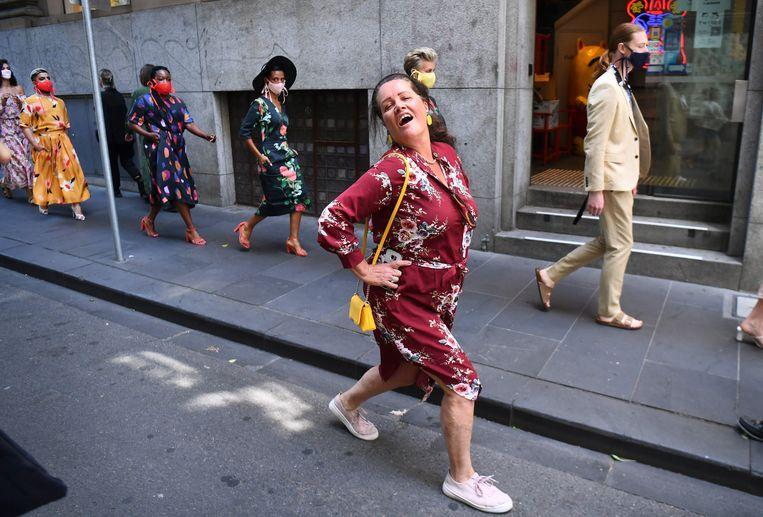 Een voorbijganger heeft besloten mee te doen aan de pop-upmodeshow van professionele modellen in de straten van Melbourne en zet haar beste beentje voor. De openluchtshow was gisteren een van de evenementen tijdens de Fashion Week in de Australische stad.  Beeld AFP