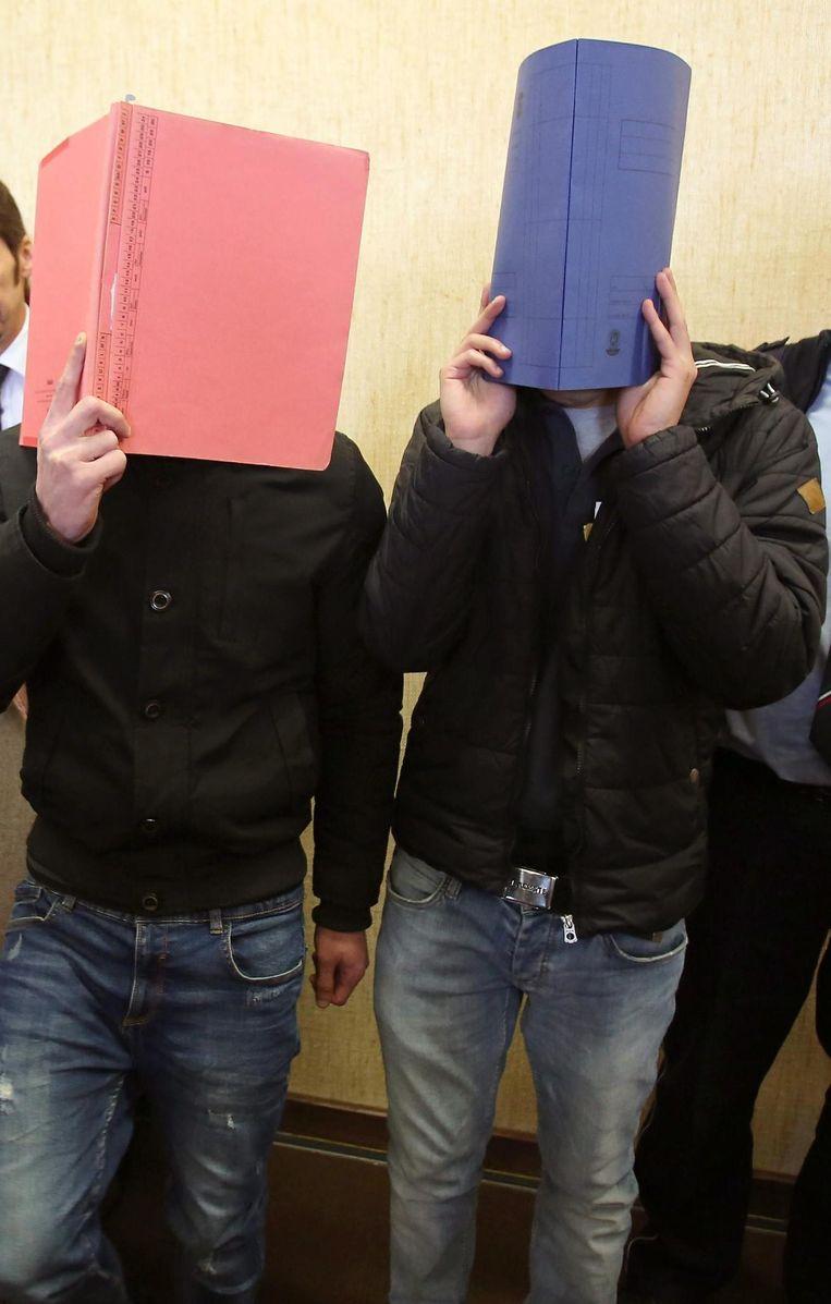 Twee van de jonge beklaagden, met map voor het gezicht aangezien de pers talrijk aanwezig was. Beeld © epa