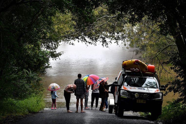 Inwoners kijken naar een ondergelopen deel van de buitenwijk Richmond, in Sydney.  Beeld AFP