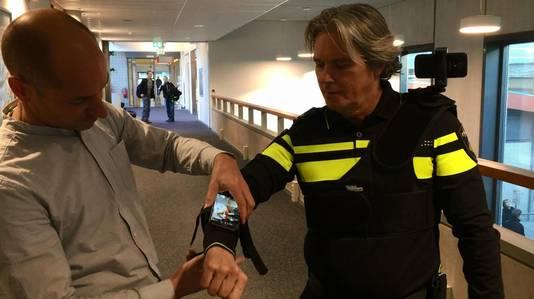 Stephan Lukosch, universitair hoofddocent systeemkunde aan de TU Delft, helpt hoofdinspecteur Rob Kouwenhoven met het omdoen van het Augmented Reality-systeem.