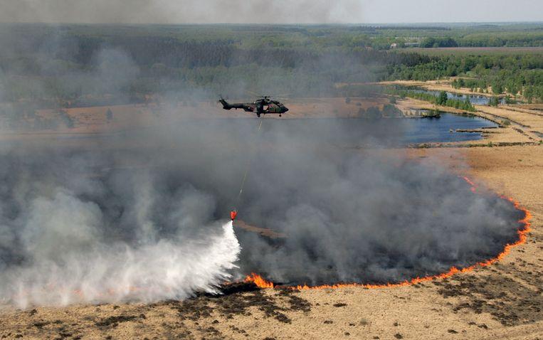 Een Cougar-transporthelikopter bestrijdt  een heidebrand in het natuurgebied Fochteloërveen bij het Drentse plaatsje Bovensmilde, 2011  Beeld ANP
