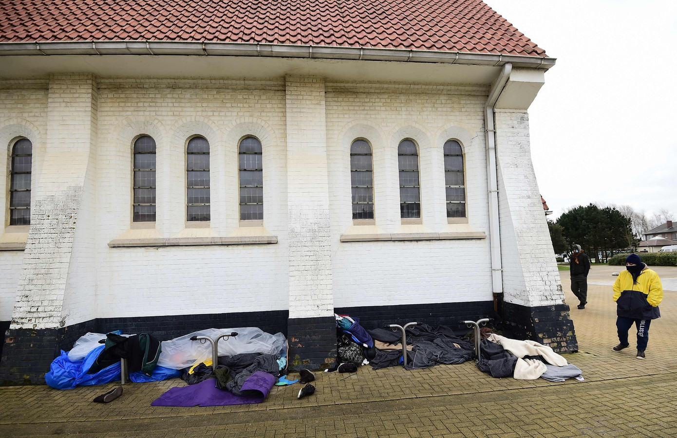 Iraanse christelijke migranten slapen tegen de gevel van de kerk in Zeebrugge.