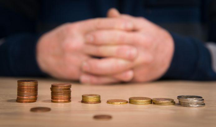 Een gepensioneerde automonteur telt de muntjes uit zijn portemonee.
