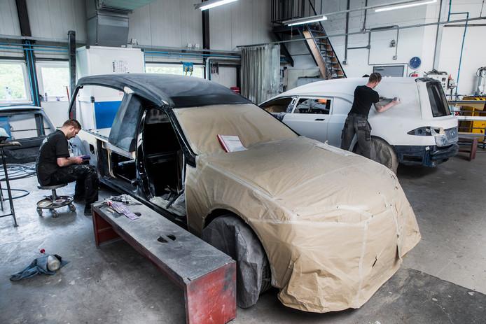 Werk aan twee rouwauto's bij Huiskamp Carrosserie. De witte wagen in de achtergrond is de Tesla.