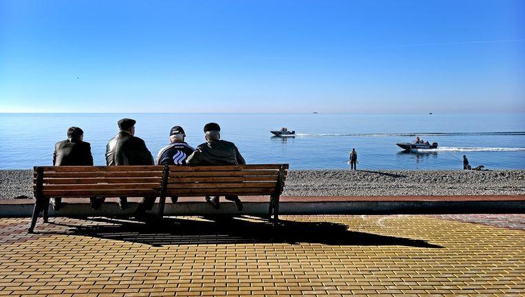 Lokale bewoners zitten op een bankje halverwege de boulevard van Sotsji. Ze zien over de Zwarte Zee twee patrouilleboten voorbijkomen. Beeld Klaas Jan van der Weij