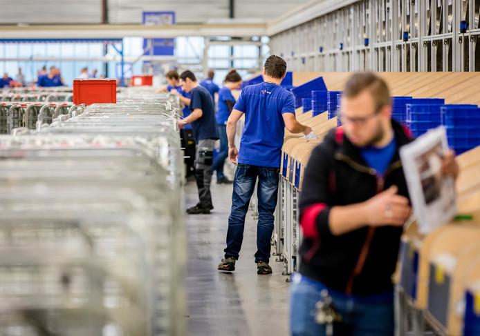 Medewerkers in een sorteercentrum van postbedrijf Sandd.