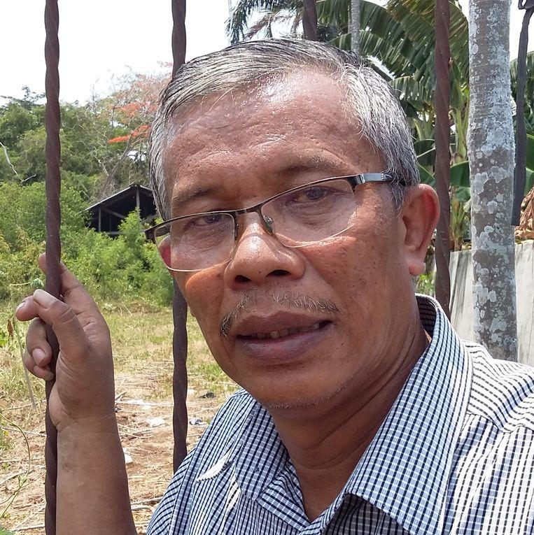 Ardus Simanjuntak  bij het hek om het terrein waar hij een kerk wil bouwen. Beeld