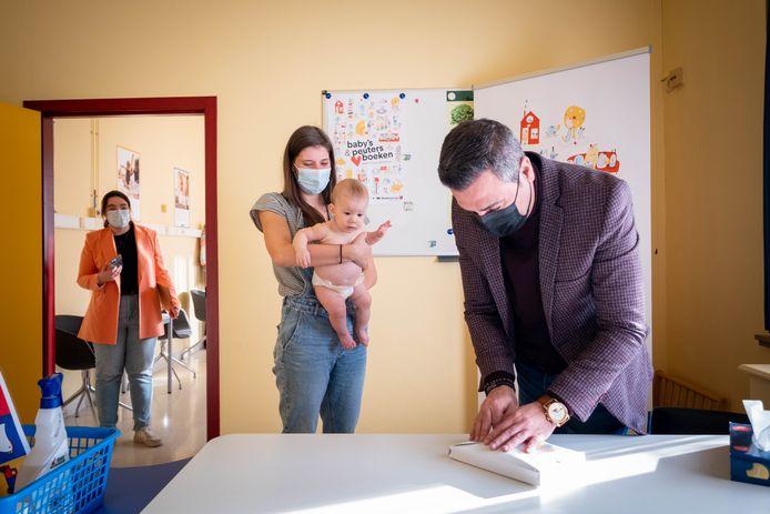Schepen Murat Oner overhandigt heet eerste boekstartpakket van de gemeente aan Lowie Foqué en zijn mama Lieselot Van der Taelen.