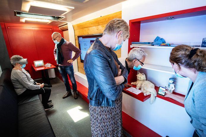 Zorgmedewerkers proberen in de experimenteerbus een VR-bril uit en krijgen uitleg over de robot en kat