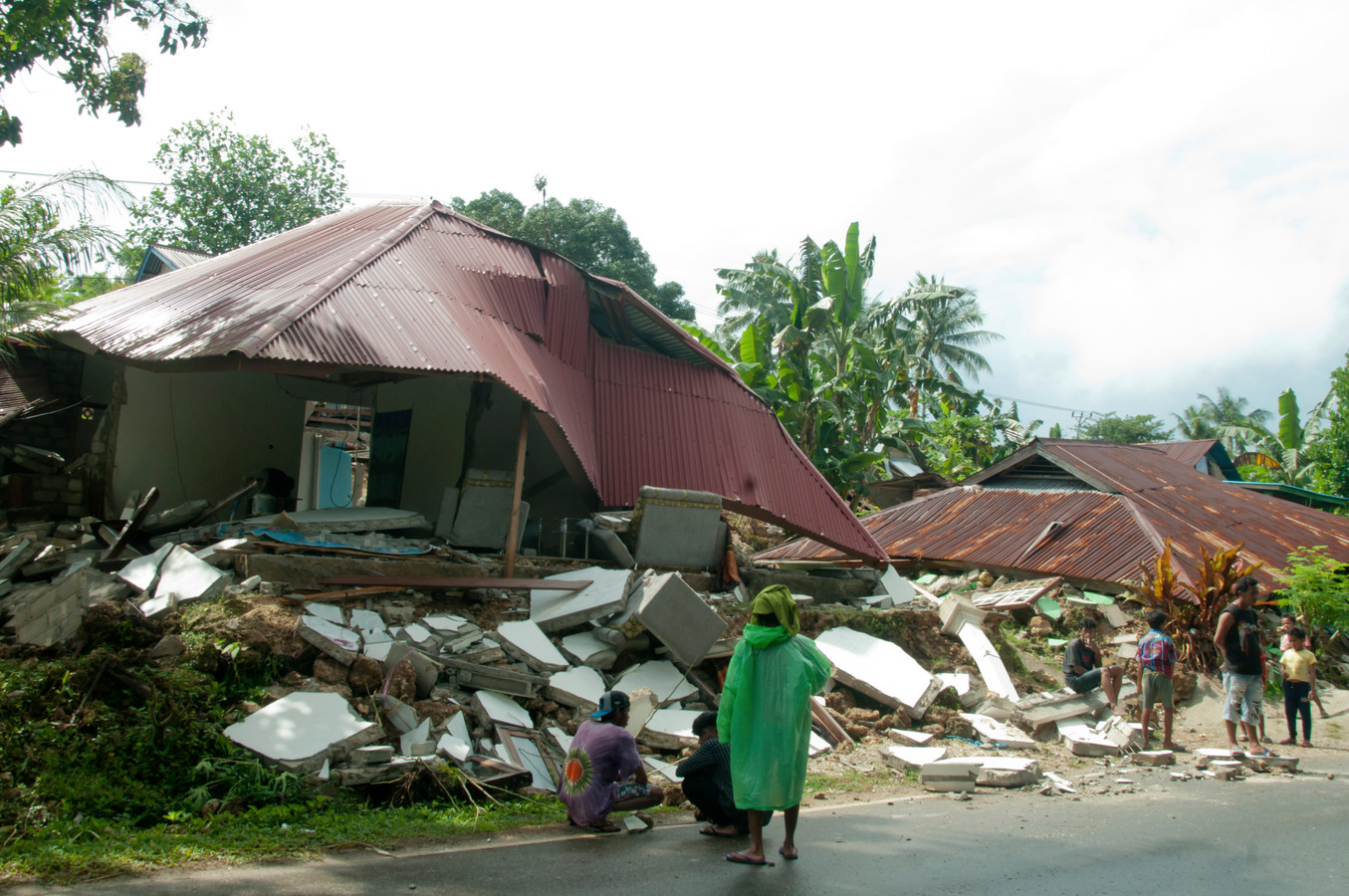 Bewoners kijken naar de restanten van hun woningen.