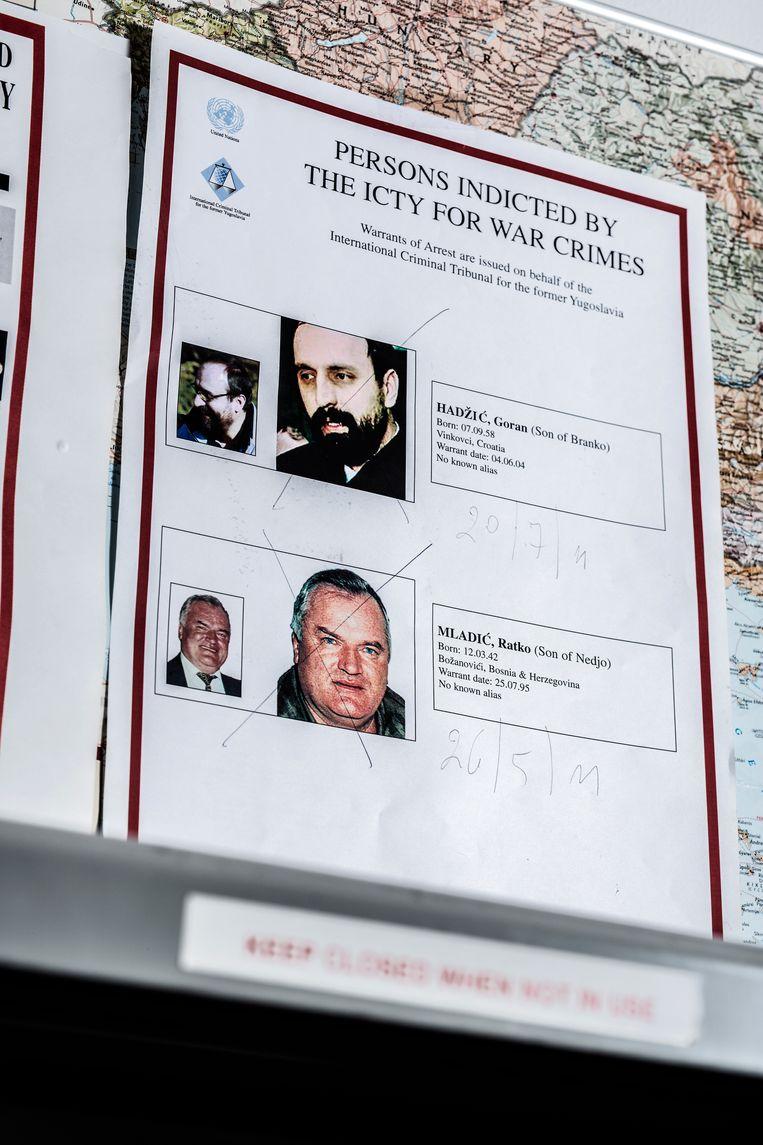 Wanneer een hoofdverdachte werd opgepakt, werd een dik kruis over zijn foto gezet. Beeld Franky Verdickt