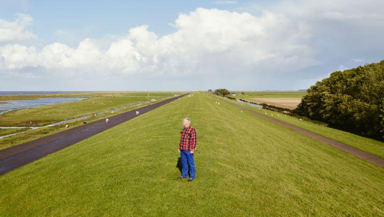 John Körmeling in het gebied in Groningen waar zijn volledig vlakke weg wordt aangelegd. 'Je merkt er straks eigenlijk geen hol van.' Beeld Jeroen Hofman
