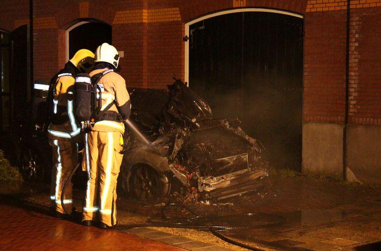Brandweermannen bij een van de auto's van Harold Halewijn, de fractieleider van GroenLinks van de gemeente Wormerland. Beeld anp
