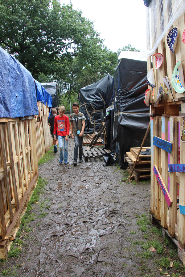 Stijn en Matthijs dwalen tussen de ingepakte hutten van Veghel in Hout. Op donderdagavond blijven er zo'n 300 kinderen in hun hut slapen. Wel droog onder een zeiltje.