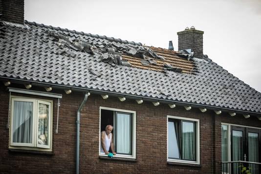 Een man praat met een buurtbewoner. Op het dak van zijn woning in Rheden is de schade die de storm aanrichtte duidelijk te zien.