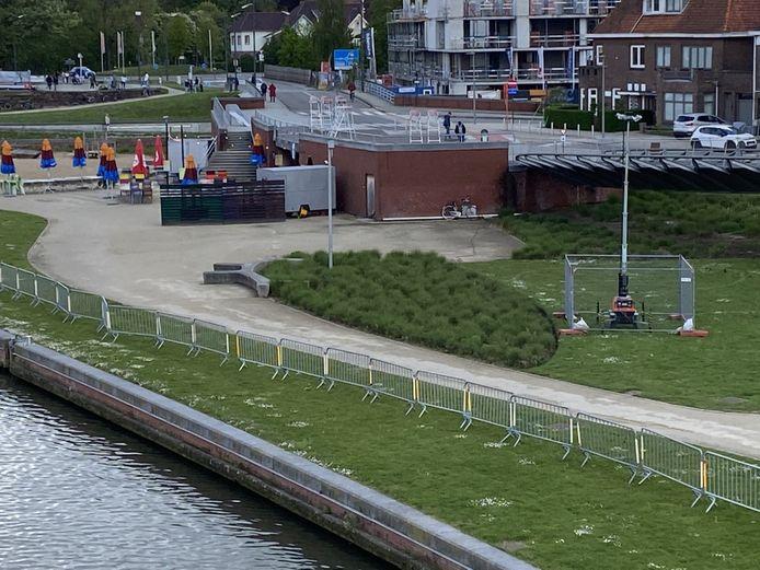 Onderaan de dranghekken langs de Leie, op Budabeach. Rechts, de mast met verlichting