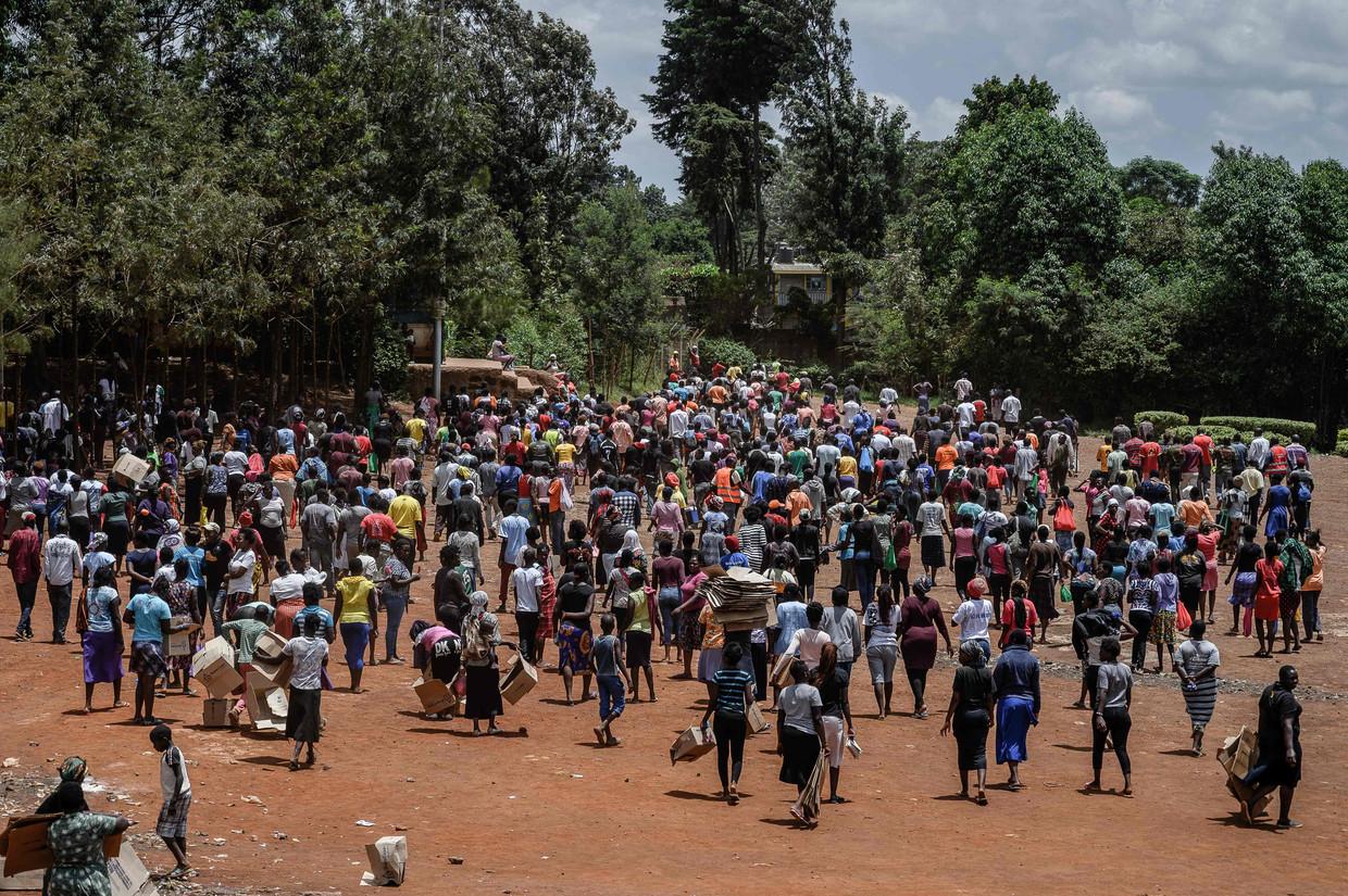 Een Keniaanse vrijwilligersorganisatie distribueert bloem, bonen en melk aan zo'n negenhonderd bewoners van een krottenwijk in Nairobi. Beeld Gordwin Odhiambo / AFP