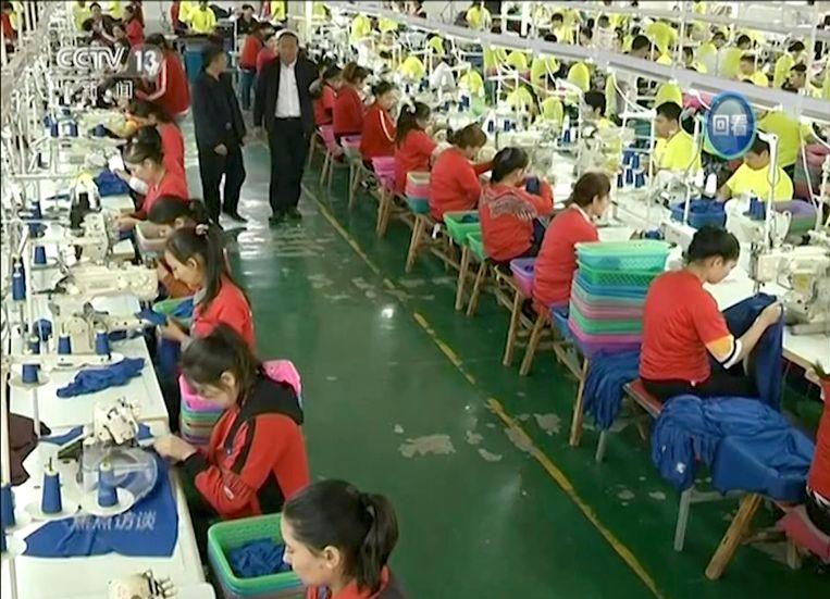 De Chinese staats-tv toont moslims die in Xinjiang opgeleid worden tot textielwerker. Beeld AP