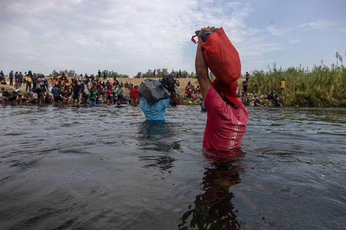 Mensen waden door de rivier om voedsel naar het migrantenkamp te brengen.