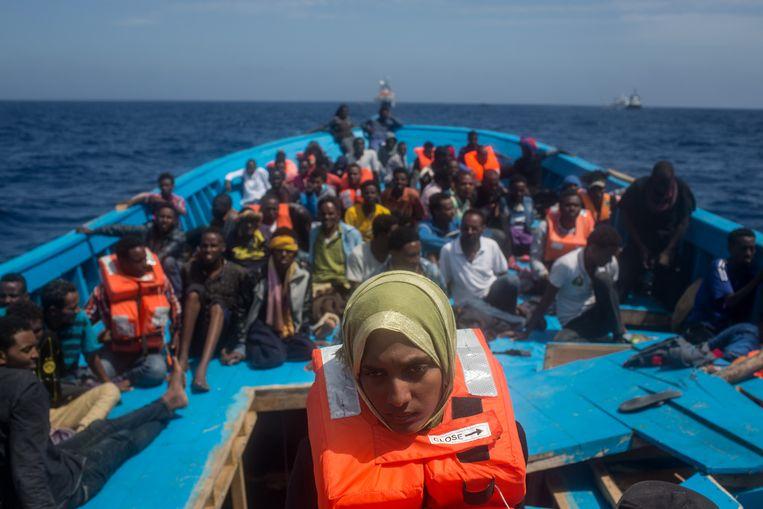 Vluchtelingen en migranten wachten in een houten boot voor de kust van het Italiaanse eiland Lampedusa tot ze aan boord kunnen van het schip van het Migrant Offshore Aid Station (MOAS). Beeld Getty Images