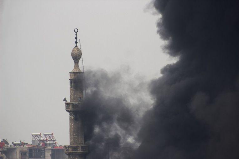 Brand in een minaret in Jobar, afgelopen woensdag bij het begin van het offensief. Beeld reuters
