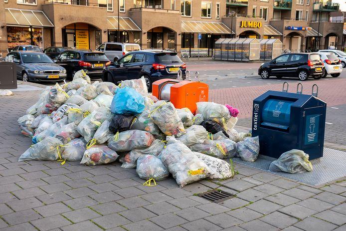 Een berg zakken met PBD-afval (plastic, blik en drinkpakken) naast de container, bij winkelcentrum Ussen.