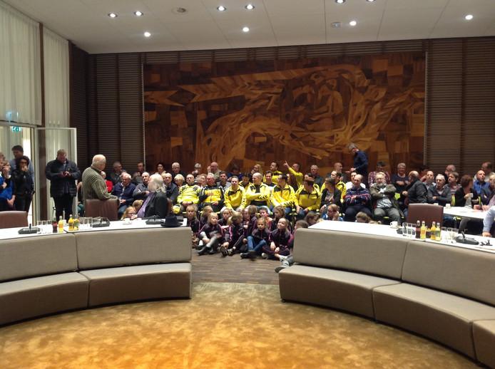 Een volle publieke tribune met sporters tijdens de raadsvergadering.