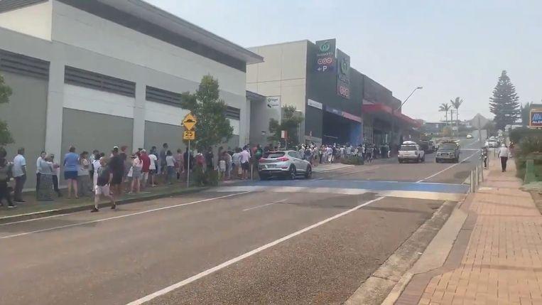Mensen staan buiten in de rij voor een supermarkt.