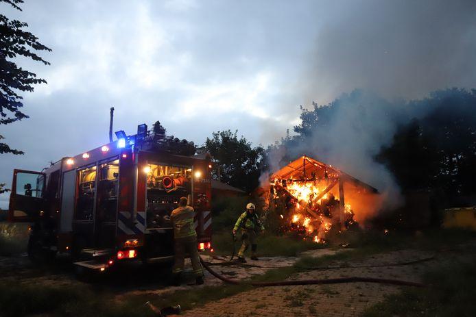 Brandweerlieden blussen de hooiberg in Doornspijk.