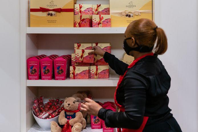 Een werkneemster van een Godiva-winkel in Atlanta stapelt een pralinedoos. De winkel telt af naar Valentijn en is aan de uitverkoop begonnen.