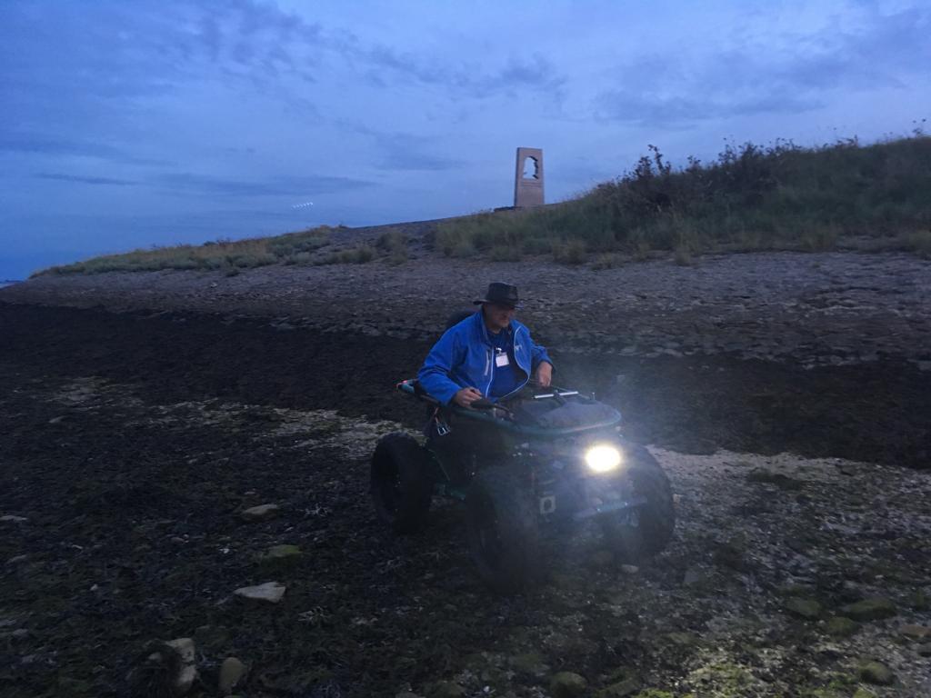 Rien Pronk op het strandje van Burghsluism dat vol stenen en wier ligt. Maar ook, zo wordt tijdens de juttersexcursie duidelijk: met vele soorten krabbetjes, alikruiken, zeewier, schelpjes en meer