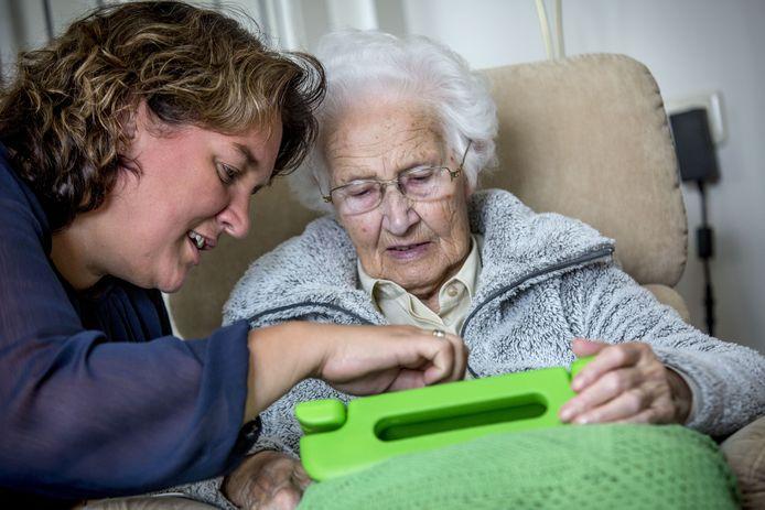 Dementie-coach Eefje van Keeken van ZorgAccent en Mevrouw Hendertink met de tablet.