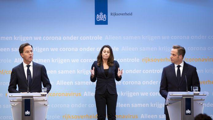 De vertrouwde opstelling tijdens de coronapersconferenties. Links premier Mark Rutte, rechts minister Hugo de Jonge (Volksgezondheid), en in het middel gebartentolk Irma Sluis