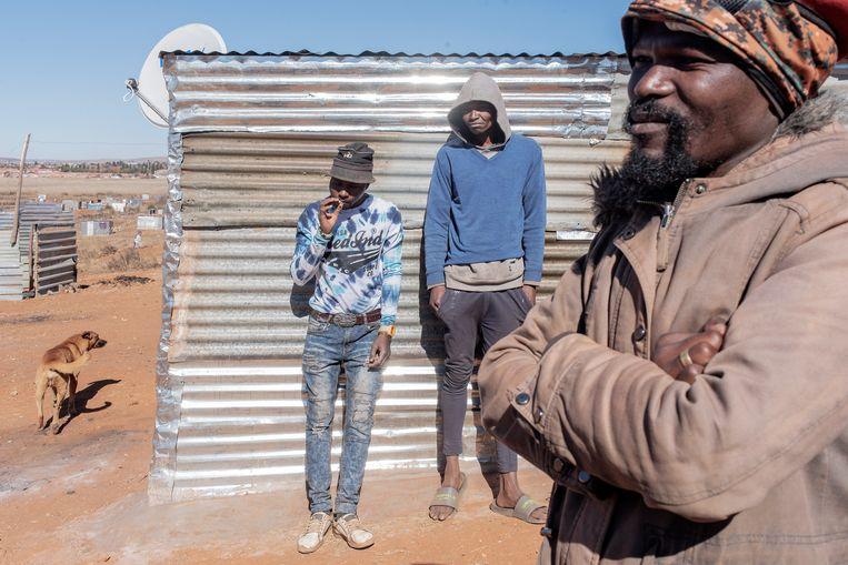 Bongani Ngubane (rechts) in de illegale nederzetting die hij oprichtte bij Johannesburg.  Beeld Luca Sola