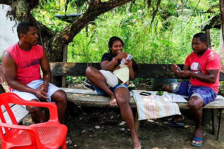 Bewoners van Coquí nemen de dag door op een bankje aan de enige straat van het dorp. Beeld Ynske Boersma