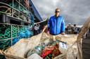 Een Zeebrugse visser verzamelt het afval in zakken.