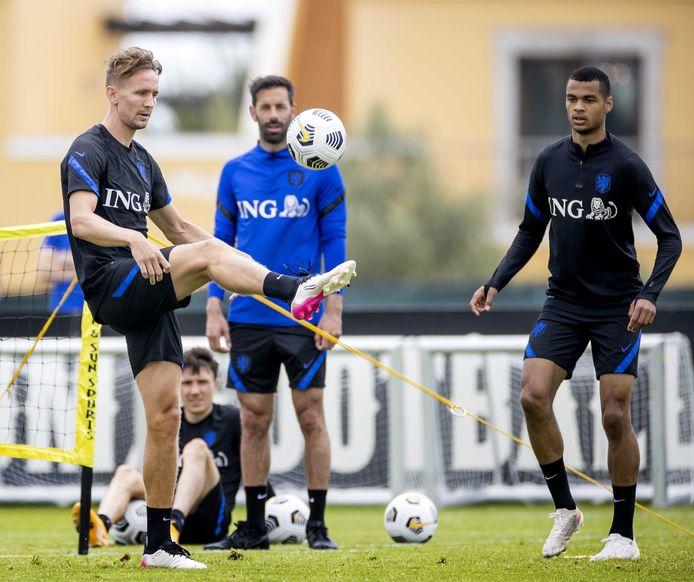 Luuk de Jong en Cody Gakpo in actie bij Oranje. Achter hen kijken Ruud van Nistelrooy en Steven Berghuis toe.