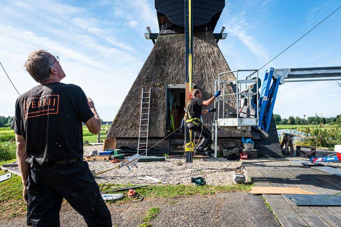 Onder toeziend oog van molenaar Arie de Gelder en oud molenaar Niek van der Horst, wordt de Westveense molen hersteld door Pieter van der Veek en Aiko van Walderveen van de firma Verbij.