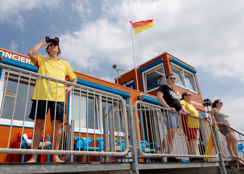 Lifeguards Bianca Koger (tweede van rechts) en Hugo Meeldijk (zwart shirt) staan op de uitkijk bij de Reddingsbrigadepost op Strand IJburg. Beeld Lin Woldendorp