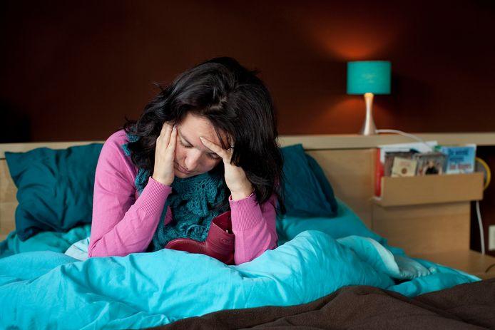 Een vrouw ligt ziek op bed. Foto ter illustratie.