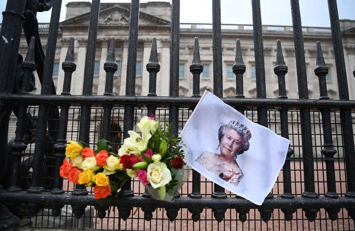 Een foto van de Britse koningin Elizabeth en bloemen aan het hek bij Buckingham Palace.