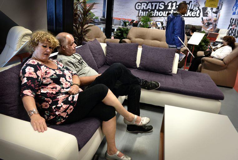 Bezoekers van de Seats and Sofas testen een bank in de winkel. Beeld Marcel van den Bergh / de Volkskrant