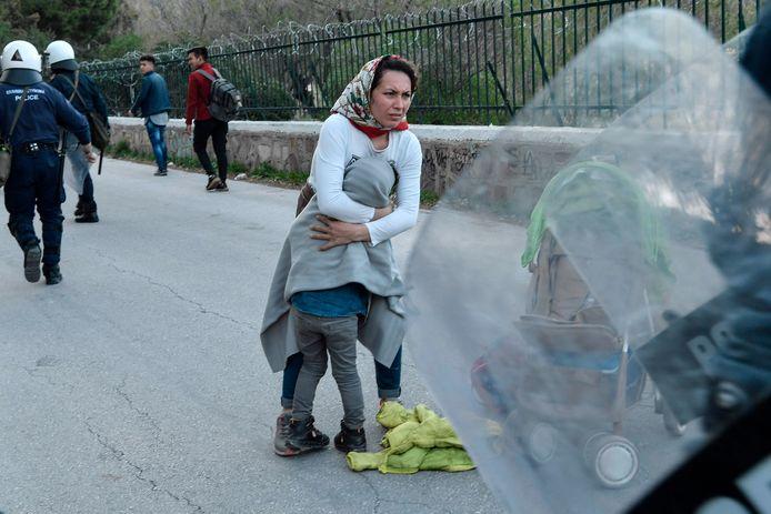 Een vrouw beschermt haar kind aan de Grieks-Turkse grens.