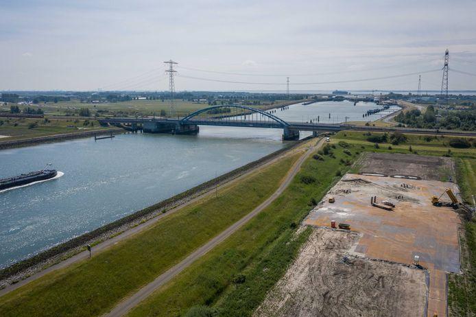 Naast de Vlakebrug worden de fundamenten gemaakt voor nieuwe hoogspanningsmasten. Op de achtergrond de bestaande vakwerkmasten.