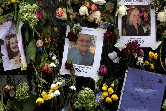 Een gedenkmuur nabij de rampplek met bloemen en foto's van slachtoffers en vermisten.