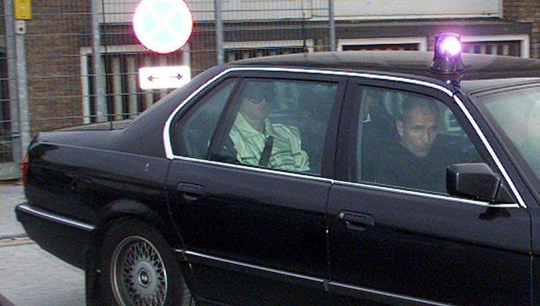 Een auto met rechts achterin topcrimineel Mink K. verlaat in 2000 onder zware bewaking het gerechtsgebouw in Amsterdam Osdorp. Beeld Archieffoto anp