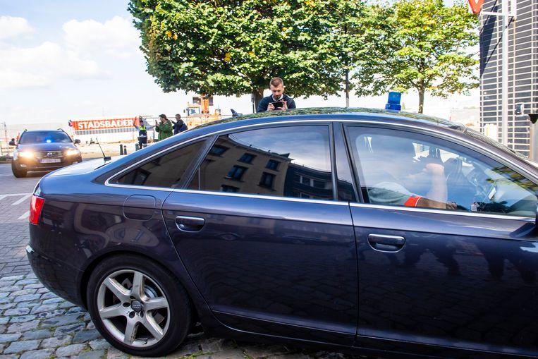 Politiewagens brengen Fouad Belkacem naar de rechtbank.